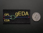 Rectangular embroidered badge with a diode schematic in green and blue, and the words GPL, EDA, gEDA in yellow, over a black background. Shown next to a quarter for scale.