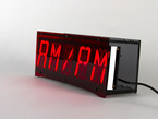 "Front of clock showing ""AM / PM"" text on display"
