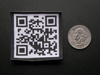 Square embroidered badge with a QR code in black on a white background, with black trimming. Shown next to a quarter for scale.