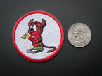 Circular embroidered badge with the BSD Daemon logo of a sad little red devil holding a pitchfork, over a white background, with red trim. Shown next to a quarter for scale.