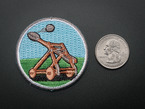 Circular embroidered badge with brown catapult mid-fling over an abstracted blue sky and green grass background. Badge is trimmed in grey and shown next to a quarter for scale.