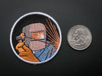 Circular embroidered badge showing the bust of an active welder in grey mask, orange safety gloves and blue coveralls with a corona of radiating orange sparks, over a black background. Badge is trimmed in white and shown next to a quarter for scale.