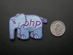 Embroidered badge in the shape of the php elephant logo. Light blue with the letters PHP and outlines in purple. Next to a quarter for scale.