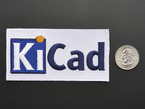 Rectangular embroidered badge with the letters KICA in blue and black on a white background, next to a quarter for scale.
