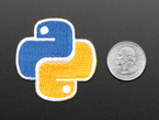 Rounded cross shaped embroidered badge of the yellow and blue Python Foundation logo. Next to a quarter for scale.