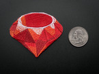Embroidered trianglesque shaped badged of ruby programming logo, in red, with pink and white highlights. Next to a quarter for scale.