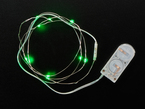 Coil of thin flexible wire with lit up embedded green LED 'fairy' lights attached to battery holder