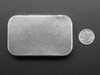 Common-size hinged mint tin case, closed next to US Quarter