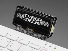 Extreme closeup of black and white OLED display assembled onto Cyberdeck bonnet. The display reads: CYBDERDECK in a cyberpunk font.