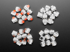 Top down view of four piles of Kailh key switches in Red, Black, Brown, and Black variations.