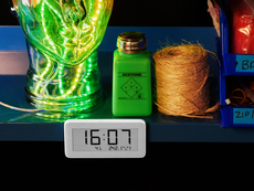 Shot of a work station shelf populated with electronic tools and a clear glass head filled with glowing LED strips. The eInk clock sits below reading the time, temperature, and humidity.