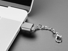 Angled shot of a microSD card reader with a key chain plugged into a laptop port.