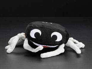 Angled shot of friendly black plushie in the form of an electrical component, Hans the 555 timer chip.