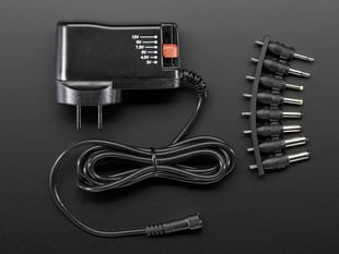 Wall wart power supply with adjustable voltage and many tips