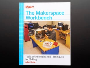 "Front cover of ""The Makerspace Workbench"" by Adam Kemp. Cover photograph features a white man behind a workbench tinkering with computer guts."