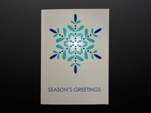 Front of Seasons Greetings card with snowflake design, and lit LED.