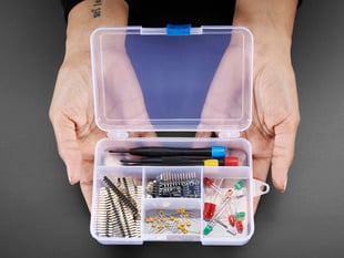 Two hands holding Latching 5-Compartment Storage Box full of assorted components