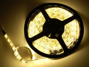 Spool of flexible LED strip lit up warm white
