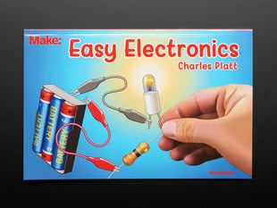 "Front cover of ""Easy Electronics"" by Charles Platt. Closeup of a hand attaching an LED to a battery pack."