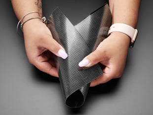 A Black woman holds a loosely folded Flexible Protoboard - 20cm x 30cm.