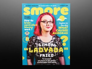 Topdown shot of Smore magazine cover. A bespeckled white woman, Limor Fried a.k.a. Ladyada, in black clothes with pink, shoulder-length hair is on the cover.