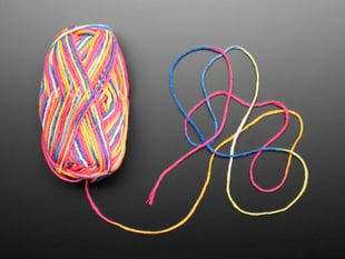 Top-down shot of a bundle skein of rainbow-colored yarn. One end of the yarn pulled from the skein.