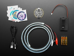 Top view shot of Adafruit + Cartoon Network Cosplay Introductory Kit; Stickers, Circuit Playground Express, Neopixal Strip w/ Alligator Clip-on, 3 AAA Battery & case.