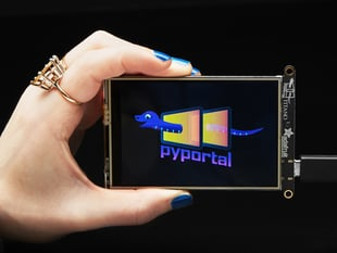 """Hand holding PyPortal Titano development board with SAMD51, ESP32 Wifi, and 3.5"""" touchscreen TFT display."""