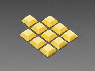 Angled shot of 10 dark yellow plastic keycaps.