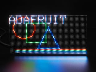 """Front on view of an RGB Matrix panel displaying """"Adafruit"""" along with geometric shapes."""