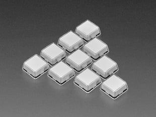 Angled shot of ten white plastic keycaps.