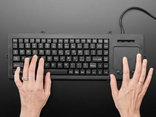 Top view of a white woman's hands typing on full-size keyboard with trackpad.