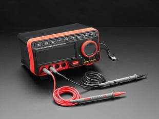 Angled shot of digital multimeter with two test lead probes.