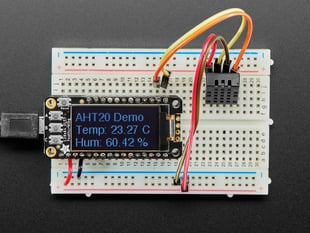 Top view of DHT20 sensor wired to a breadboard with an FeatherWing OLED display. The OLED shows the data from the temperature-humidity sensor.