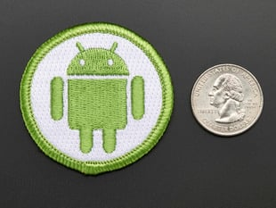 Circular embroidered badge with Android's green robot on white background with green trim. Shown next to a quarter for scale.