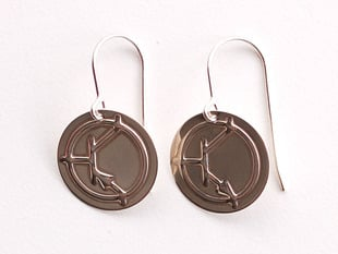 Close up of silver earrings. One  showing an NPN symbol and the other showing a PNP symbol