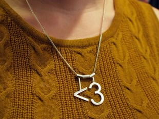 "model wearing silver necklace with ""<3"" heart symbol"