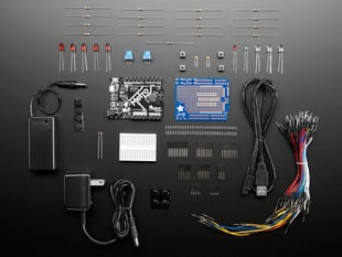 Adafruit Metro 328 Starter Pack showing kit contents, with boards, PCBs, wires and power supplies