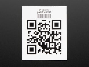 Square sticker with a QR code in black on a white background, with black trimming. Mounted on white paper with barcode.