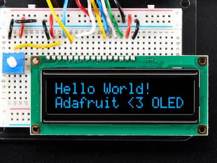 "Wired up 16x2 OLED with blue on black text ""Hello World! Adafruit <3 OLED"""