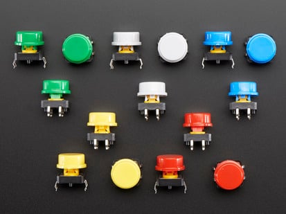 Top-down shot of 15 colorful round tactile button switches in green, yellow, red, blue, and white.