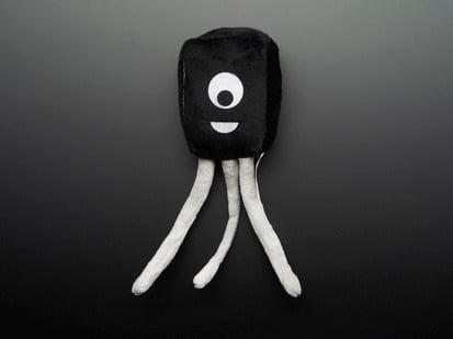 Topdown shot of friendly black plushie in the shape of an electrical transistor, Connie the transistor.