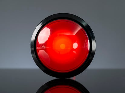 Head-on shot of illuminated massive red 100mm arcade button.