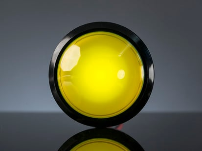 Head-on shot of illuminated massive yellow 100mm arcade button.