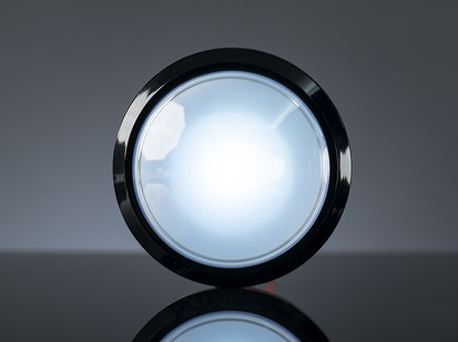Head-on shot of illuminated massive white 100mm arcade button.