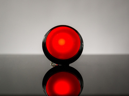 head-on shot of illuminated large red arcade button with LED.