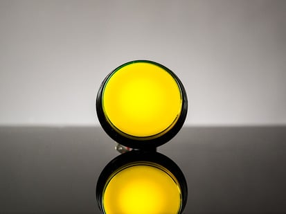 head-on shot of illuminated large yellow arcade button with LED.