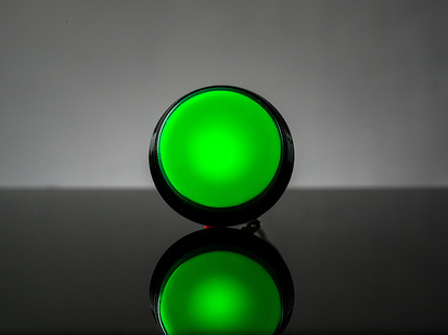 head-on shot of illuminated large green arcade button with LED.