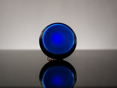 Head-on shot of illuminated large blue arcade button 60mm