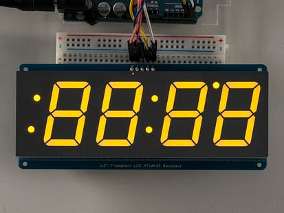 Huge yellow 7-segment clock display soldered to backpack with all segments lit
